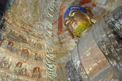 Yungang Grottoes near Datong in Shanxi Province, China. Large ancient statue of Buddha in a cave at Yungang with gold face and blue hair. Yungang Buddhist cave art and sculptures UNESCO world heritage