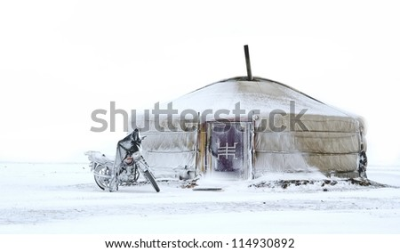 yurt standing in the snow with motorcycle in front of it, Mongolia