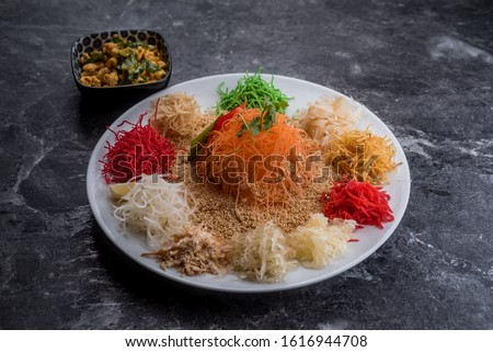 Yusheng, yee sang or yuu sahng, or Prosperity Toss is a Cantonese-style raw fish salad. It consists of strips of raw fish, mixed with shredded vegetables and a variety of sauces and condiments. Photo stock ©