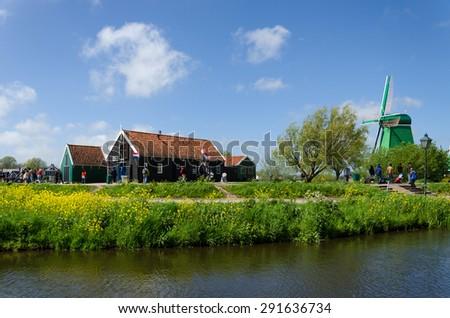Zaanse Schans, Netherlands - May 5, 2015: Tourist visit Windmills and rural houses in Zaanse Schans, Netherlands. This village is a popular touristic destination in Netherlands