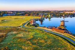 Zaanse Schans rural windmills, fields and river landscape, North Holland, Netherlands, aerial view in sunrise light