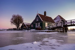 Zaanse Schans windmill village during winter with snowy landscape, snow covered wooden historical windmills Zaanse Schans Netherlands Holland. Europe