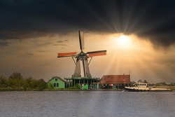 Zaanse Schans, Zaandam Netherlands - typical windmill in Holland with water in front and small boat floating on it - stormy sky with sunset