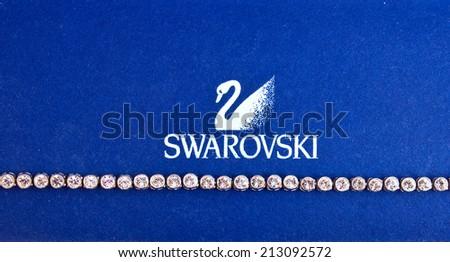 ZAGREB , CROATIA - AUGUST 24 , 2014 : Swarovski jewelry brand logo next to necklace close up , product shot