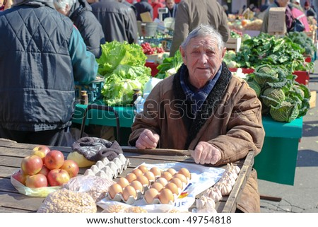 ZAGREB - MARCH 6: Old man selling eggs and apples at outdoor Dolac market on March 06, 2010 in Zagreb, Croatia. Dolac is the largest farmer's market in Zagreb.
