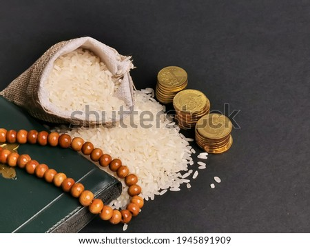 Zakat concept. Selective focus rice in sack with coins,rosary and Koran. Zakat is a mandatory process for Muslims and is regarded as a form of worship. Photo stock ©