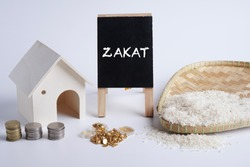ZAKAT word coin stacked, rice grain in bowl, gold dinar jewellery and mini house on whitebackground. Muslim concept for zakat property, gold /jewellery, income and