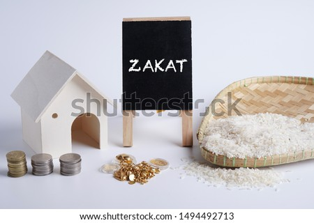 """ZAKAT word coin stacked, rice grain in bowl, gold dinar jewellery and mini house on whitebackground. Muslim concept for zakat property, gold /jewellery, income and """"fitrah"""" zakat."""