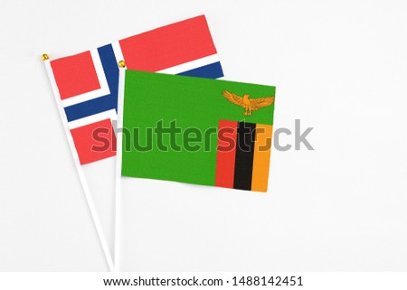 Zambia and Norway stick flags on white background. High quality fabric, miniature national flag. Peaceful global concept.White floor for copy space. #1488142451
