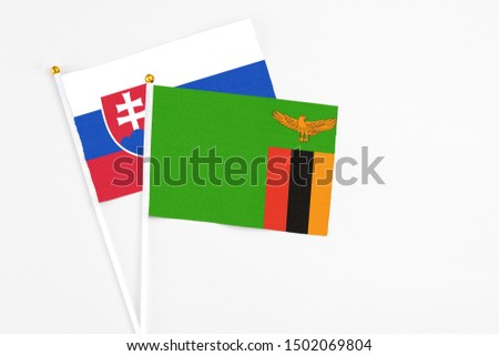 Zambia and Slovakia stick flags on white background. High quality fabric, miniature national flag. Peaceful global concept.White floor for copy space. #1502069804