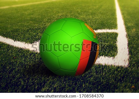Zambia flag on ball at corner kick position, soccer field background. National football theme on green grass. ストックフォト ©
