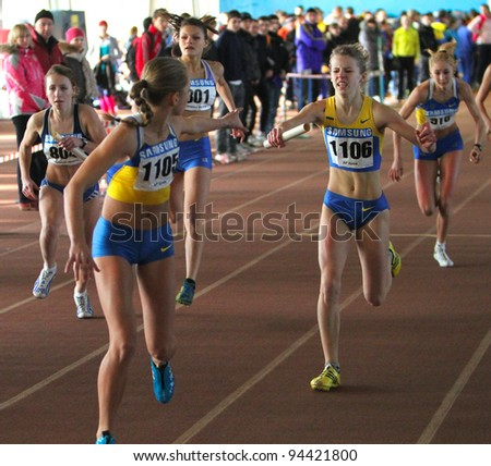 ZAPORIZHIA,UKRAINE - JAN 31: (L-R) Mudrova Aleksandra, Mironova Anastasia, Fesuk Marina run the relay race on Ukainian Junior Track and Field Championships on January 31, 2012 in Zaporizhia, Ukraine