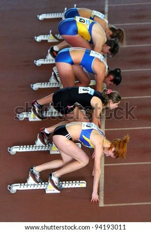 ZAPORIZHIA, UKRAINE - JAN.27: Unidentified girls on the start of the 60 meters dash on the Ukrainian Cup in Athletics on January 27, 2012 in Zaporizhia, Ukraine.