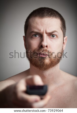 Zapping concept - annoyed man with tv remote control