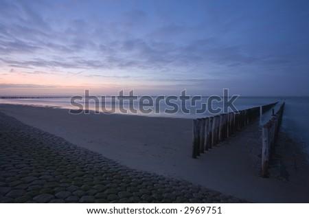 zee en avondzon met golfbreker Stockfoto ©