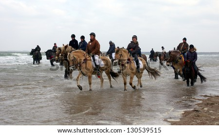 "ZEELAND,NETHERLANDS - FEB. 23: A group of men on horses participate in the annual event ""strao""; a historic celebration where horses feet are washed in the sea on February 23, 2013 in Zeeland."