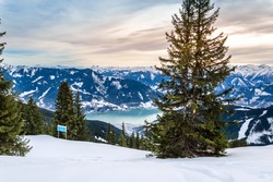 Zell am See and Schmitten town at Zeller lake in winter. View from Schmittenhohe mountain, snowy ski resort slope in the Alps mountains, Austria. Stunning landscape, snow and sunset sky near Kaprun