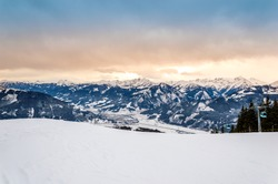 Zell am See at Zeller lake in winter. View from Schmittenhohe mountain, snowy slope of ski resort in the Alps mountains, Austria. Stunning landscape with snow and sunset sky near Kaprun