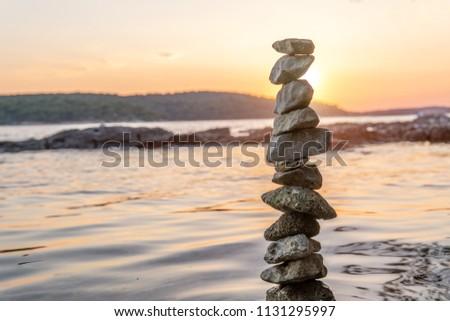 Zen balanced stones stacked on sea coast at sunset. Balance and equilibrium concept.