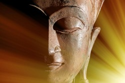Zen Buddhism. Divine light rays of spiritual enlightenment or astral projection on buddha head statue.