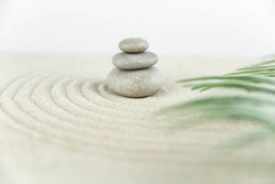 Zen garden. Pyramids of white and gray zen stones on the white sand with abstract wave drawings. Concept of harmony, balance and meditation, spa, massage, relax.