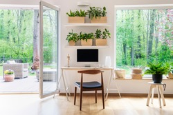 Zen home office with computer in a beautiful, spacious living room interior with plants and an outside view through big windows
