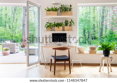 Photo of  Zen home office with computer in a beautiful, spacious living room interior with plants and an outside view through big windows