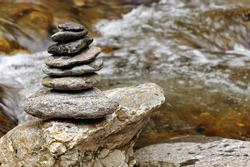 Zen meditation concept. Pyramid of stones (cairn) placed near river water