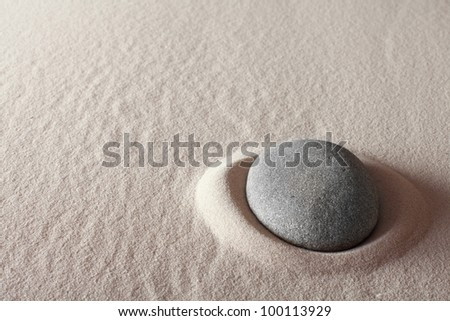 zen meditation stone relaxation or concentration point to focus and to meditate round grey rock in sand simplicity and purity spa background
