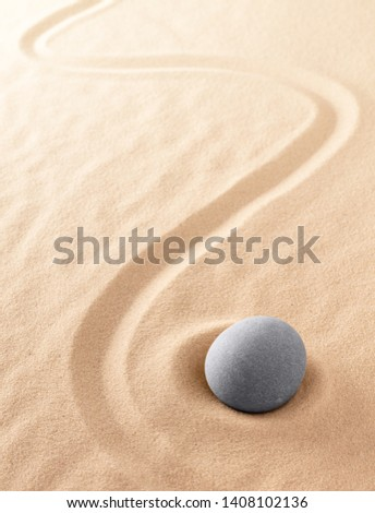 Zen meditation stone to focus and concentrate for a quiet peace of mind. Spiritual raked sand background texture. Concept for harmony purity and spirituality.  Stockfoto ©