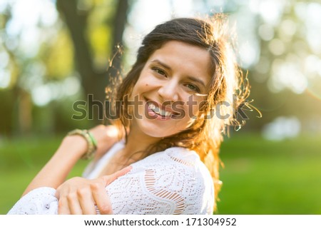 Zen multi-ethnic girl enjoying warmth in a summer sunset