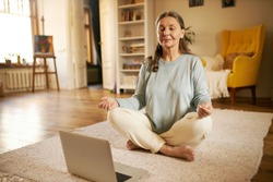 Zen, peace, balance, concentration and technology concept. Attractive senior woman sitting on carpet in front of open laptop keeping eyes closed and legs crossed, meditating to nature sounds
