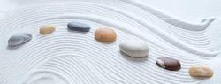 Zen pebbles on white sand pattern