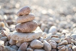 Zen pyramid from spa stones on a blurred sea background. Sea stones on the coast. Sea coast. Place for text. Sea view. A stone structure on the beach