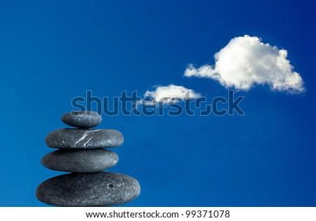 zen shot of balanced stones and a bright blue sky