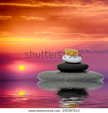 Zen spa concept background - Zen massage stones at sunset reflected in water #290387012
