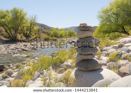 Zen stability concept, relaxation environment, outdoors tranquility, simplicity in nature. Meditation scene next to a river on a soft spring summer sunny day with a pile of stones in perfect balance