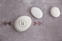 Zen stone with pause symbol, and fast forward, rewind on either side