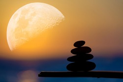 Zen stones pyramid on the background of the big moon and the sea