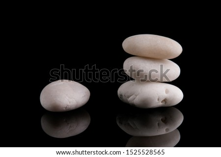 Zen Stones. White stones piled on top of each other. White stones on a black background.