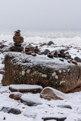 Zen stones with small and big stones at the snowy beach a seaside in winter after snow storm in Tuja in Latvia