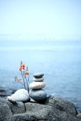 Zen style balanced stones on beach. Rock sculpture stone stacking. A stone pyramid on sea shore. Stones balance on a background of sea and blue sky.