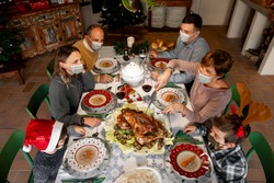 Zenith angle of a Family gathered around the table at Christmas Thanksgiving dinner on 2020. Family members wear surgical masks to comply with the new health regulations. Covid quarantine, lockdown.