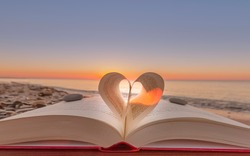 Zenith on the beach. Folded book in heart shape with sunrise.