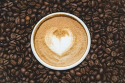 Zenith view of a cup of coffie with a drawn heart  surrounded by coffe beans