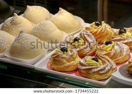 Zeppole and tette delle monache for breakfast in a shop window of an Italian bar Stock fotó ©