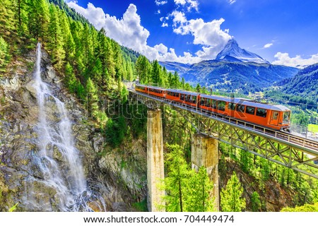 Zermatt, Switzerland. Gornergrat tourist train with waterfall, bridge and Matterhorn. Valais region.