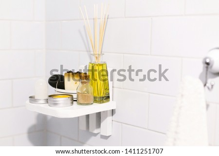 Zero waste bathroom concept. Eco natural shampoo in metal can,  deodorant, soap and ayurveda ubtan powder in glass on wooden shelf in bathroom, plastic free items. Sustainable lifestyle