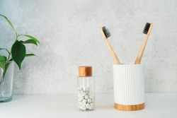 Zero waste bathroom items. Bamboo toothbrushes in recycling material holder, natural mouthwashing tabs and fresh green plants in glass. Oral care essentials. Eco-friendly home. Minimalism. Copy space.