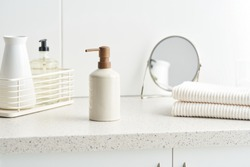 Zero waste bottle of soap and stack of clean cotton towels placed on cupboard near vase and mirror in bathroom